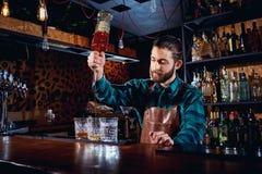 Der Kellner mit einem Bart gießt Alkohol in Gläser in einer Bar Stockfotografie