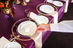 Der Kellner setzt die Platte auf dem Tisch stockfotos
