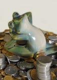 Der keramische junge Frosch sitzt auf einer kleinen Gruppe Münzen Lizenzfreie Stockbilder