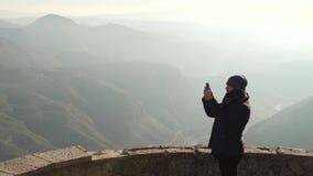Der Kerl auf der Aussichtsplattform betrachtet eine schöne Ansicht der Berge im Dunst stock video
