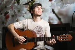 Der Kerl auf dem Bett, das klassische Gitarre spielt Lizenzfreie Stockfotos