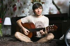 Der Kerl auf dem Bett, das klassische Gitarre spielt Stockfotos
