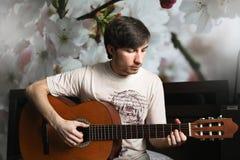Der Kerl auf dem Bett, das klassische Gitarre spielt Stockfotografie