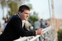 Der Kerl auf der Brücke und Blicke in den Abstand Lizenzfreies Stockfoto