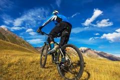 Der Kerl auf einem Fahrrad in den Bergen Herbst in den Bergen Lizenzfreie Stockbilder