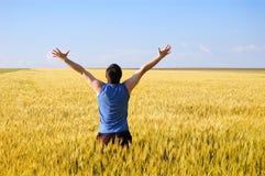 Der Kerl auf einem Herbstgebiet freut sich zu einem Getreide Lizenzfreies Stockbild