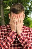 Der Kerl bedeckte sein Gesicht mit seinen Händen, die Mannschreie Lizenzfreie Stockfotos