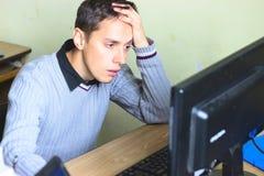 Der Kerl betrachtet Computer traurig Stockfotos