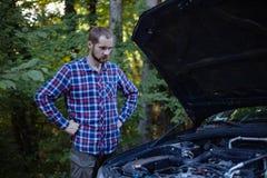 Der Kerl betrachtet den Automotor stockfotos