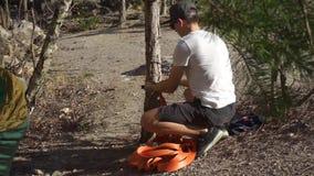 Der Kerl bindet das Seil am Baum stock video footage