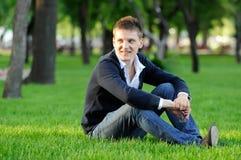 Der Kerl, der auf dem Gras sitzt Lizenzfreie Stockbilder