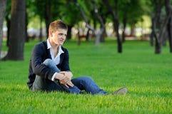 Der Kerl, der auf dem Gras sitzt Stockfotografie