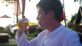 Der Kerl, der auf dem Strand und dem Getränkbier sitzt Langer Berührungsschuß Stockbild