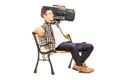 Der Kerl, der ein boombox auf seiner Schulter hält und auf einem hölzernen sitzt, ist Stockbild
