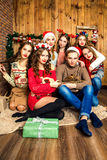 Der Kerl in der Firma von sechs Frauen im Raum mit Weihnachten d Lizenzfreie Stockfotos