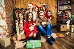 Der Kerl in der Firma von sechs Frauen im Raum mit Weihnachten d Stockfotografie