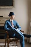 Der Kerl in der Klage, die auf Stuhl sitzt und weg schaut Stockfoto