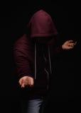 Der Kerl, der unter Alkoholismus in einer Haube auf einem schwarzen Hintergrund leidet Schlechtes, Alkohol, ungesund, Risikokonze Lizenzfreie Stockfotografie