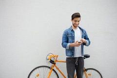 Der Kerl in einer blauen Denimjacke, die auf Wandhintergrund steht junger Mann nahe orange Fahrrad Lächelnder Student mit Tasche Lizenzfreie Stockfotografie
