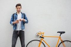 Der Kerl in einer blauen Denimjacke, die auf Wandhintergrund steht junger Mann nahe orange Fahrrad Lächelnder Student mit Tasche Lizenzfreies Stockfoto