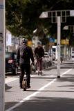 Der Kerl fährt auf den Bürgersteig auf einem monowheel stockfotografie
