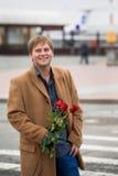 Der Kerl am Flughafen mit Rosen lizenzfreie stockfotos