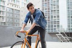Der Kerl geht zur Stadt auf einem Fahrrad in der Blue Jeans-Jacke junger Mann ein orange Verlegenheitsfahrrad lizenzfreies stockfoto