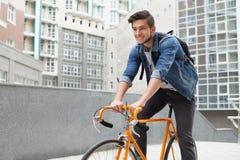 Der Kerl geht zur Stadt auf einem Fahrrad in der Blue Jeans-Jacke junger Mann ein orange Verlegenheitsfahrrad Stockbilder