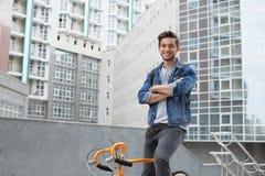 Der Kerl geht zur Stadt auf einem Fahrrad in der Blue Jeans-Jacke junger Mann ein orange Verlegenheitsfahrrad stockfotografie