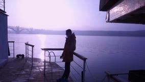 Der Kerl in der gelben Jacke raucht eine Zigarette Morgen, Fluss, Nebel, Natur, Felsen Haus auf dem Wasser stock video