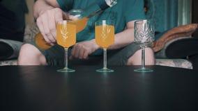 Der Kerl gießt herein drei Stapel, die auf dem Tisch gelbes Cocktail stehen Die Kamera nimmt eine Nahaufnahme Langsames Play-back stock footage