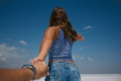 Der Kerl hält die Mädchen ` s Hand Follow-me zu Stockfotos