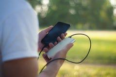 Der Kerl hält ein tragbares Ladegerät mit einem Smartphone in seiner Hand Mann auf einem Hintergrund der Natur mit Grüns Lizenzfreies Stockfoto