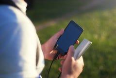 Der Kerl hält ein tragbares Ladegerät mit einem Smartphone in seiner Hand Mann auf einem Hintergrund der Natur mit Grüns Lizenzfreies Stockbild