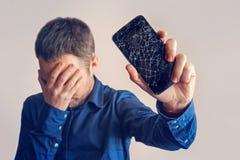 Der Kerl hält einen schwarzen Smartphone mit einer defekten Anzeige stockbild