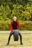 Der Kerl hebt den hohen Reifen an Stockfoto