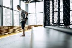 Der Kerl, der im grauen T-Shirt gekleidet wird, dehnt seine Arme in der boxenden Turnhalle mit panoramischen Fenstern aus lizenzfreie stockfotografie