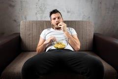 Der Kerl im Hemd liegt auf der Couch, isst Chips und passt einen Sportkanal auf Das Konzept der Trägheit stockfotografie