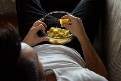 Der Kerl im Hemd liegt auf der Couch, isst Chips und passt einen Sportkanal auf Das Konzept der Trägheit lizenzfreies stockfoto