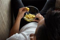 Der Kerl im Hemd liegt auf der Couch, isst Chips und passt einen Sportkanal auf Das Konzept der Tr?gheit stockfoto