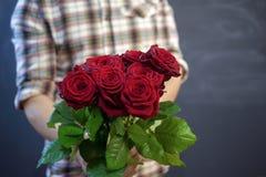 Der Kerl im karierten Hemd hält einen Blumenstrauß von roten Rosen in seiner Hand, Fokus auf Blumen stockfotografie