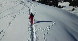 Der Kerl im Skianzug ist auf einer schneebedeckten Spur in den Bergen Über den Wolken stock video footage