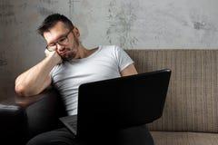 Der Kerl im wei?en Hemd, das auf der Couch sitzt, schlief bei der Arbeit ?ber einen Laptop ein Das Konzept der Tr?gheit, Apathie lizenzfreie stockfotografie