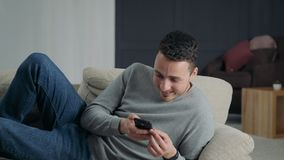 Der Kerl lacht das Lügen auf dem Sofa mit dem Telefon stock video