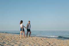 Der Kerl leitet das Mädchen in dem Meer Stockbild