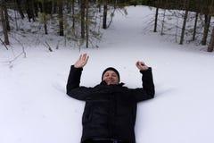 Der Kerl liegt auf seinem zurück im Schnee Der Mann fiel in die Schneewehe mit den ausgestreckten Armen lizenzfreies stockfoto