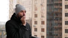 Der Kerl mit dem Bart steht auf dem Balkon, der eine Zigarette raucht stock footage