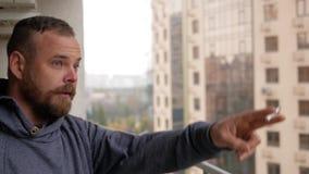 Der Kerl mit dem Bart steht auf dem Balkon, raucht und zeigt auf den Himmel stock video footage