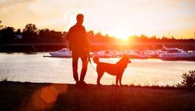 Der Kerl mit dem Hund, der den Sonnenuntergang auf dem Dock aufpasst ukraine Stockfotos
