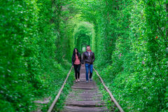 Der Kerl mit dem Mädchen gudlyayut Eisenbahntunnel des Liebesfrühlingswaldes Stockfoto